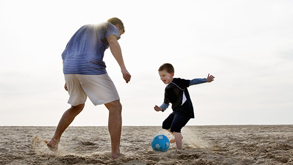 Man and boy play football on the beach