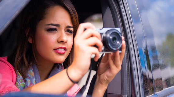 woman taking photograph from car window