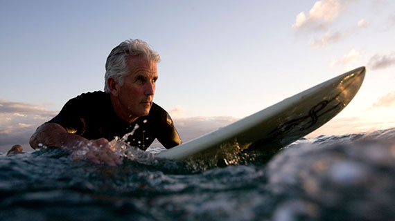 grey haired man surfing