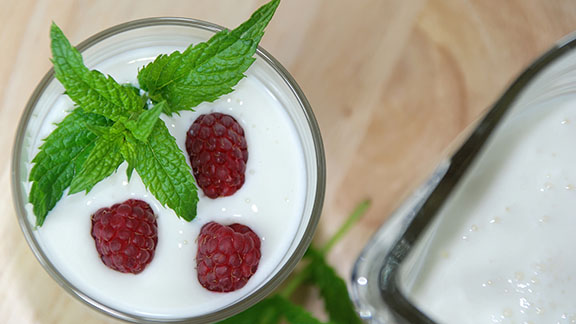 Raspberries and mint leaves in probiotic yoghurt