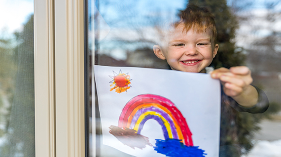 young boy holding rainbow picture in window