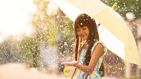 Happy young girl holding an umbrella