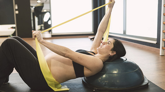 Pregnant woman on exercise ball, using a resistance band