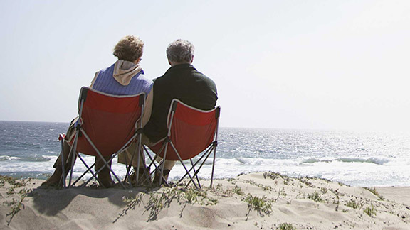 Elderly couple sitting by the beach