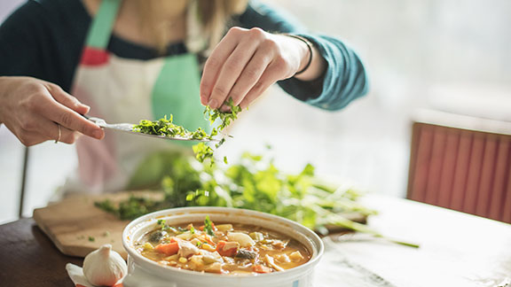 Woman adding herbs into a cooking pot