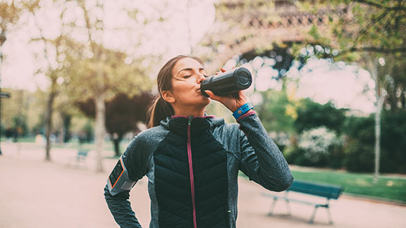 Woman in sports gear drinking water by the Eiffel Tower