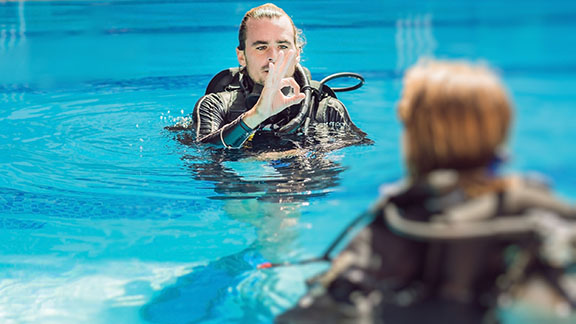 A scuba diving instructor teaching the OK sign to a beginner diver
