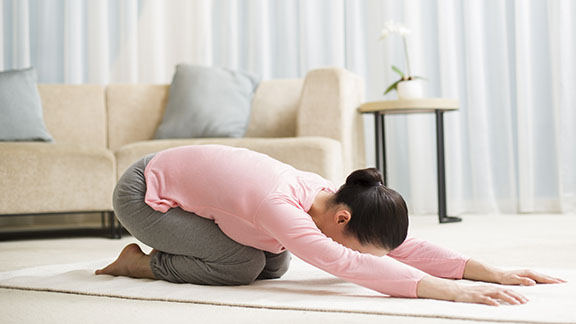 Woman practising yoga in hotel room