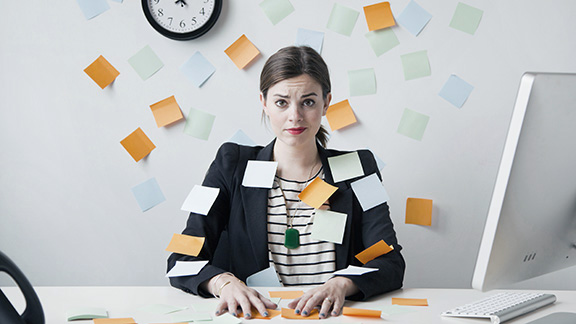 Woman at desk, covered in sticky notes